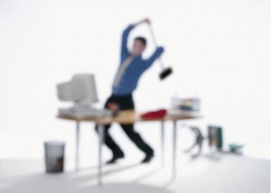 Photo of a frustrated office worker destroying his computer with a sledge hammer illustrating that we need to take regular breaks on the job to support our well being.