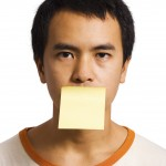 "Young Man With A Post It Note On His Mouth representing ""your word is your bond"""