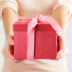 Woman giving a red gift box with pink ribbon repreent kidness, grace and gratitude.