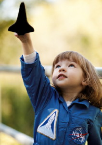 Child wearing a NASA costume and holding a toy space shuttle representing that we all need something to inspire us in our work and a part of our well-being.