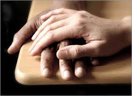One hand gently resting on another to illustrate compassion which is essential for well=being