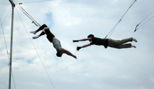 Trapeeze acrobats practicing, show trust for one another.