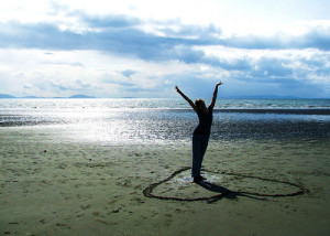 Person on beach with heart scrapped into the sand an example os self-compassion