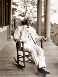 Mark Twain sitting in a wroking chair on a porch