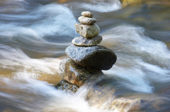Pile of rocks in rushing water represents keep calm and carry on